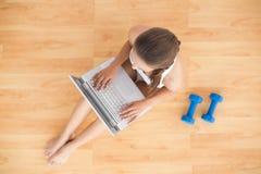 使用膝上型计算机的运动的浅黑肤色的男人和坐在哑铃旁边 免版税图库摄影