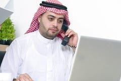 使用膝上型计算机的阿拉伯商人和谈话在电话 免版税库存图片