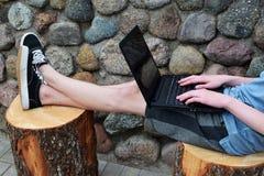 使用膝上型计算机的青少年的男孩户外 库存图片