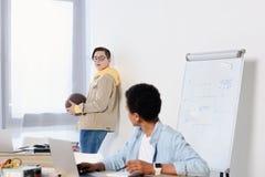 使用膝上型计算机的非裔美国人的青少年的男孩和看有篮球球的朋友 免版税库存图片