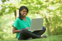 使用膝上型计算机的非洲裔美国人的少妇 免版税图库摄影