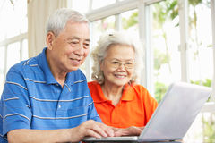 使用膝上型计算机的高级中国夫妇在家 免版税库存照片
