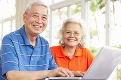 使用膝上型计算机的高级中国夫妇在家 库存照片