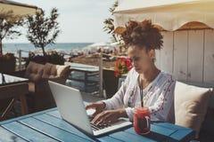 使用膝上型计算机的黑人女孩在咖啡馆在海附近 库存照片