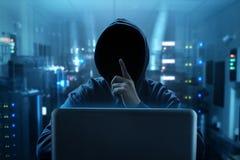 使用膝上型计算机的黑客在里切断屋子 库存照片