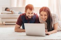 使用膝上型计算机的年轻不同种族的夫妇,当在家时说谎在地毯 免版税库存图片