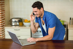 使用膝上型计算机的年轻人和谈话在电话 免版税库存照片