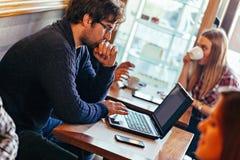 使用膝上型计算机的年轻人在咖啡馆 免版税库存照片