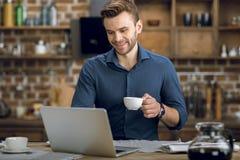 使用膝上型计算机的年轻人,当在家时喝咖啡 库存图片