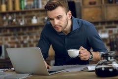 使用膝上型计算机的年轻人,当在家时喝咖啡 免版税库存图片