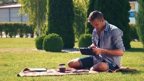使用膝上型计算机的年轻人,当坐毯子在公园时 影视素材