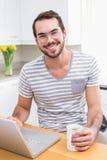 使用膝上型计算机的年轻人,当食用咖啡时 库存图片