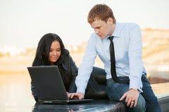 使用膝上型计算机的年轻企业夫妇 免版税图库摄影