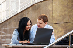 使用膝上型计算机的年轻企业夫妇 免版税库存照片