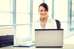 使用膝上型计算机的年轻可爱的女商人在办公室 库存照片