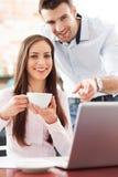 使用膝上型计算机的商人在咖啡馆 免版税库存图片