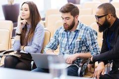 使用膝上型计算机的年轻商人坐会议 免版税库存图片