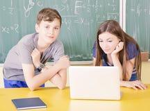 使用膝上型计算机的年轻大学生 免版税库存图片