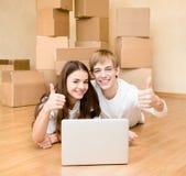 使用膝上型计算机的年轻夫妇在他们新的家庭和显示的赞许 免版税库存照片
