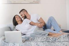 使用膝上型计算机的年轻夫妇,当拥抱在与毯子时的床上 免版税库存照片