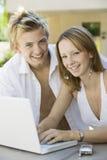 使用膝上型计算机的年轻夫妇 免版税图库摄影