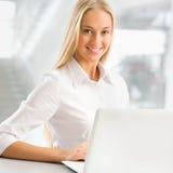 使用膝上型计算机的年轻女商人在办公室 库存照片