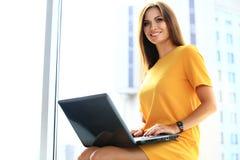 使用膝上型计算机的年轻女商人在办公室 库存图片