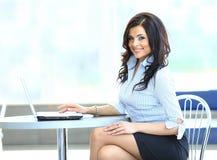 使用膝上型计算机的年轻女商人在工作书桌 库存图片