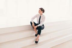 使用膝上型计算机的年轻女商人画象在办公室微笑 免版税库存图片
