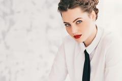 使用膝上型计算机的年轻女商人画象在办公室微笑 图库摄影