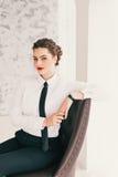 使用膝上型计算机的年轻女商人画象在办公室微笑 免版税图库摄影