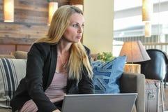 使用膝上型计算机的年轻女商人 图库摄影