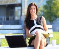 使用膝上型计算机的年轻女商人 免版税图库摄影