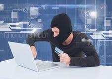 使用膝上型计算机的黑客和拿着在数字式背景前面的一张信用卡 库存照片