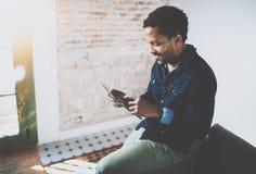 使用膝上型计算机的年轻有胡子的非洲人,当坐沙发在他的现代家庭办公室时 工作与的人的概念 库存图片