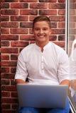 使用膝上型计算机的轻松的年轻人坐在红色增殖比的窗台 库存图片