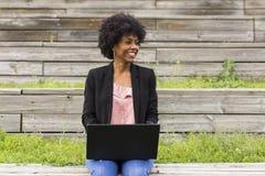 使用膝上型计算机的年轻美国黑人的妇女 绿色背景 casua 免版税图库摄影