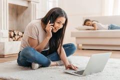 使用膝上型计算机的年轻非裔美国人的妇女和在家谈话在智能手机 库存照片