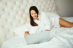 使用膝上型计算机的Beatufiul浅黑肤色的男人在床 免版税库存图片