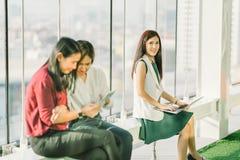 使用膝上型计算机笔记本和数字式片剂的美丽的年轻亚裔女孩在办公室期间打破在日落,现代生活方式概念 免版税库存图片