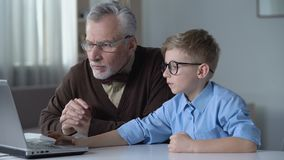 使用膝上型计算机,儿童显示祖父如何搜寻信息在互联网 股票录像