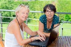 使用膝上型计算机,在庭院大阳台的两个成熟妇女朋友 免版税库存照片