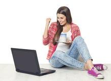 使用膝上型计算机,在笔记本,愉快的女孩计算机的成功的妇女 免版税库存图片