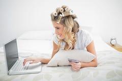 使用膝上型计算机,在网上快乐的逗人喜爱的白肤金发的购物 免版税库存照片