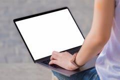 使用膝上型计算机,妇女的妇女坐与膝上型计算机的地板在腿 图库摄影