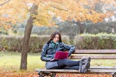 使用膝上型计算机,学生学会户外- 图库摄影