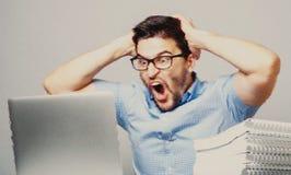 使用膝上型计算机,年轻人冲击了蓝色衬衣的人 免版税图库摄影