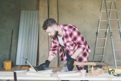 使用膝上型计算机,行家有胡子的人是木匠,建造者,设计师立场在车间,拿着轴 免版税库存图片