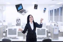 使用膝上型计算机,计算器,电话,时钟的Multitasker女实业家 免版税库存图片