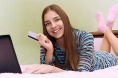 使用膝上型计算机,年轻美丽的微笑的女孩做网上购物 库存照片